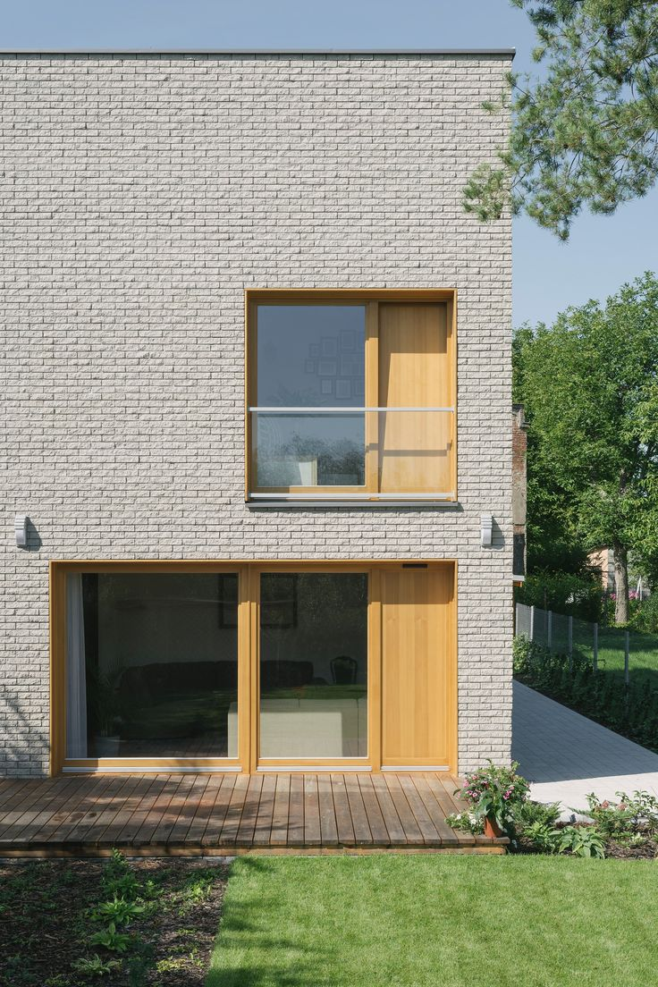 Recessed windows lined in oak interrupt the homogenous brick facades of this house in Warsaw, which local architecture studio MFRMGR designed to make the most of an awkward site.
