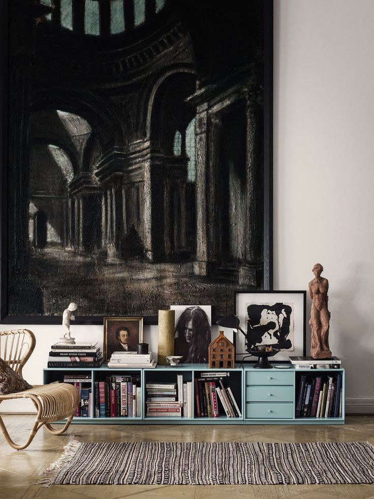 Absolutely love this layering of pics and items on a low shelf in front of a large hanging piece