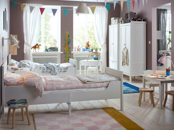 Ein Kinderzimmer mit zwei SUNDVIK Bettgestellen mit Federholzrahmen in Weiss und zwei weissen Kleiderschränken, die nebeneinanderstehen