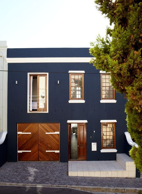Navy blue walls, white framing the windows and for garage door hinges against the warmth of frames and doors in wood is a winning combination on this house's exterior.