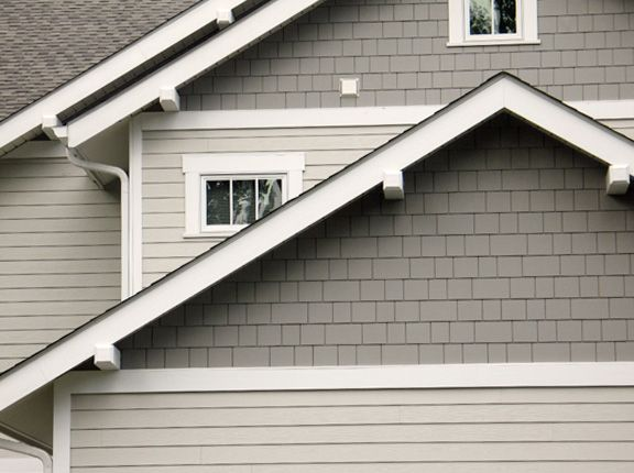 Fiber-cement shingle style around front door and above garage roof line. A couple shades darker off-white.