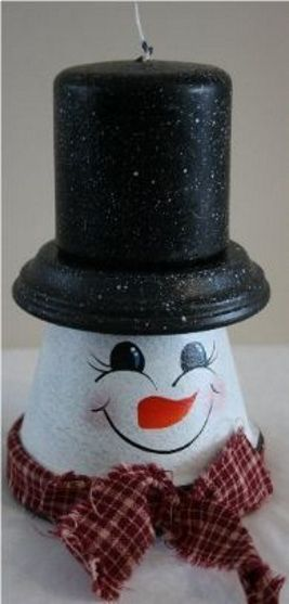 Handpainted snowman candle made from a terra cotta pot and saucer which is a hat and a black candle sits on top turning the saucer into his hat. Our snowman candle is accented with a country bow tied around his neck