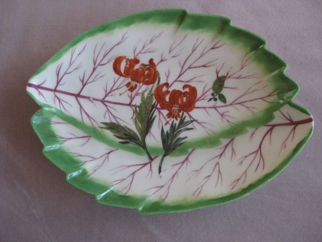 """A Chelsea plate of overlapping leaf shape and with a green border and puce veining and painted to the centre with a  red lily         .  Anchor mark   Circa  1760 Length 11"""""""