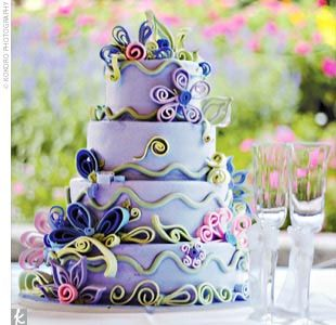 Caitlyn and Kon cut an elaborate four-tier cake iced in periwinkle blue Bavarian cream and adorned with a spectrum of stylized fondant flowers. The tiers alternated between chocolate with strawberry filling and white chocolate with chocolate Bavarian cream filling.