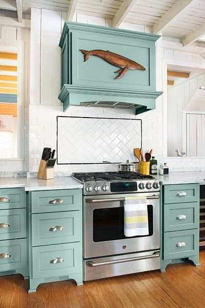 teal kitchen cabinets and matching range hood cover, marble countertops, white subway tile backsplash, beach cottage kitchen remodel
