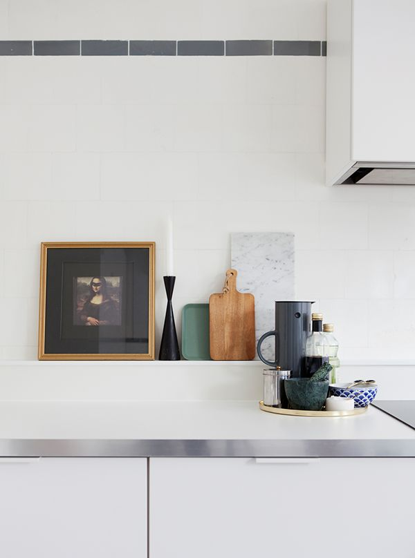 White tiles and dark grey boarder in the kitchen of a Swedish home in a former shop. Bolaget.