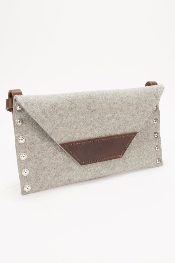 Wool felt convertible clutch bag, there is a shoulder strap which can be detached so you can use this bag as both a shoulder bag and a clutch.  The bag is made out of 3mm wool felt with Italian tanned leather trim. The strap is made out of thick leather which has been beveled and burnished to create a smooth rounded edge. The bag is assembled using pop rivets and there is a small internal pocket for your phone etc.  You can have your initials embossed on the leather strip on the front for an…