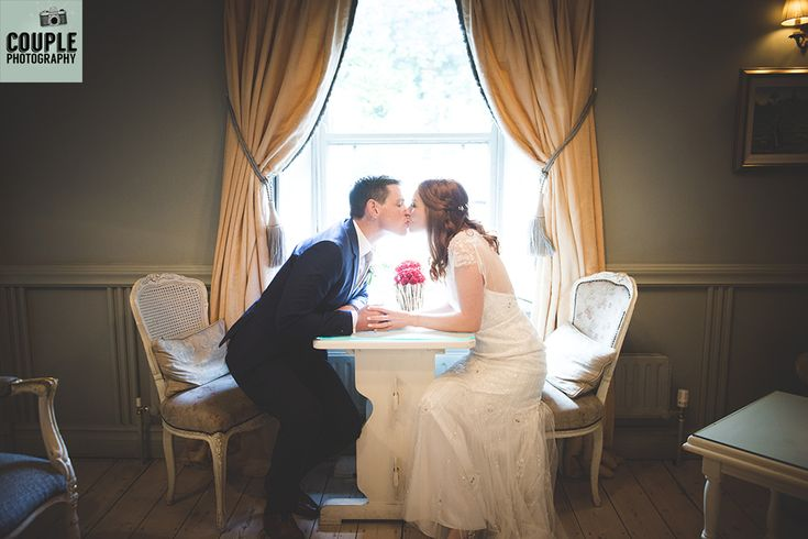 The bride & groom have a kiss by the window light. Weddings at Conyngham Arms Hotel, Slane, by Couple Photography.