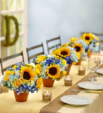 Country Wedding Centerpiece ...Bouquet of sunflower, hydrangeas,delphinium, and spray roses arranged in terra cotta pots