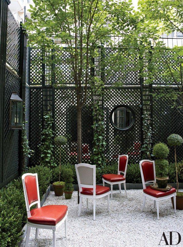 The garden is framed with mirror-backed trelliswork | archdigest.com