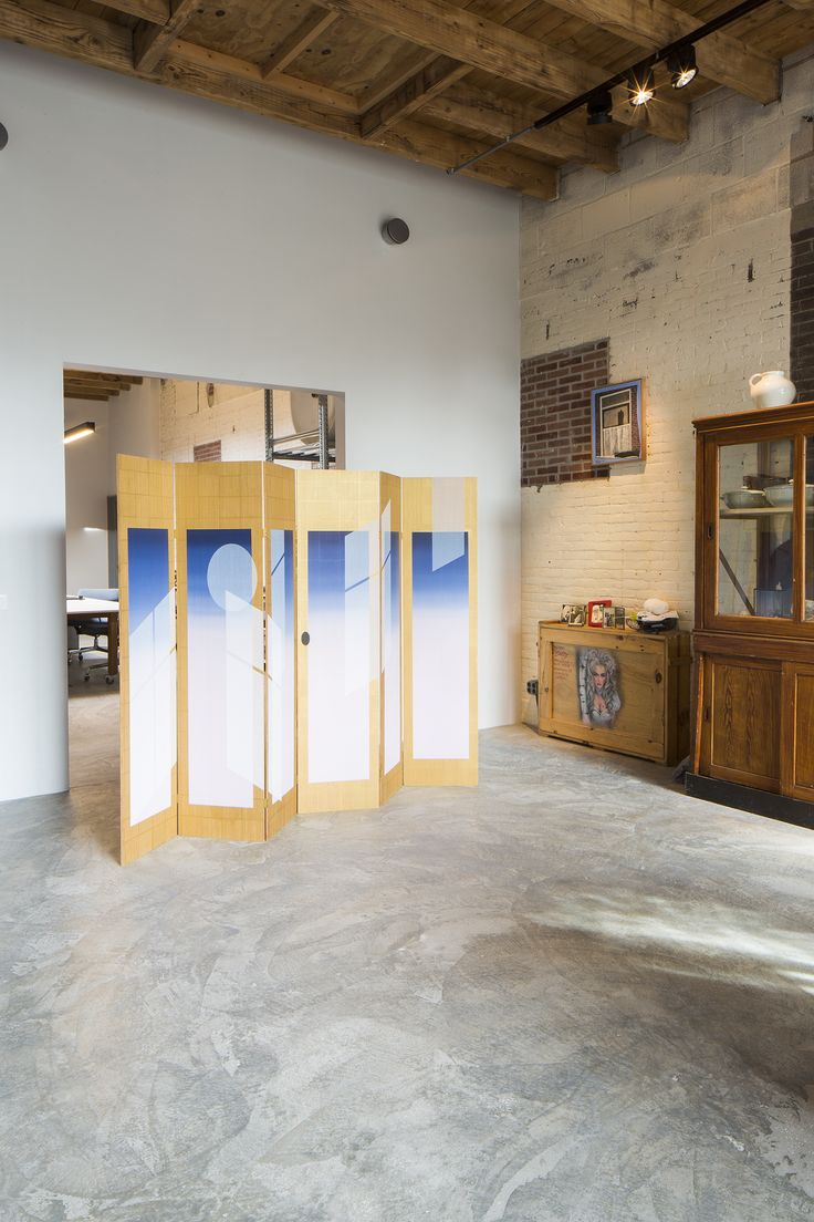 A folding room divider separating the living room from the office in
