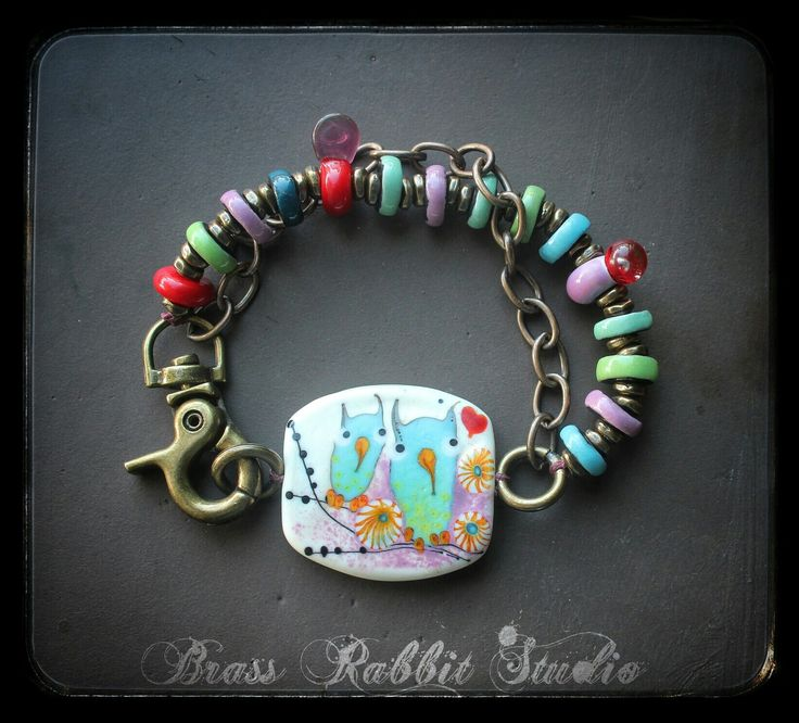 """This lampwork owl bracelet is so fun! The lamp work focal was handmade by Jasmin French and measures about 1.25""""x1"""". It is double sided with two owls on one side and just one on the other. The band has handmade porcelin discs by Joan Miller, fun little lampwork accents by Jasmin also and a Vintaj brass chain. The clasp is a large brass swivel base lobster clasp, I love the swivel feature because it makes puting on the bracelet so much easier alone."""
