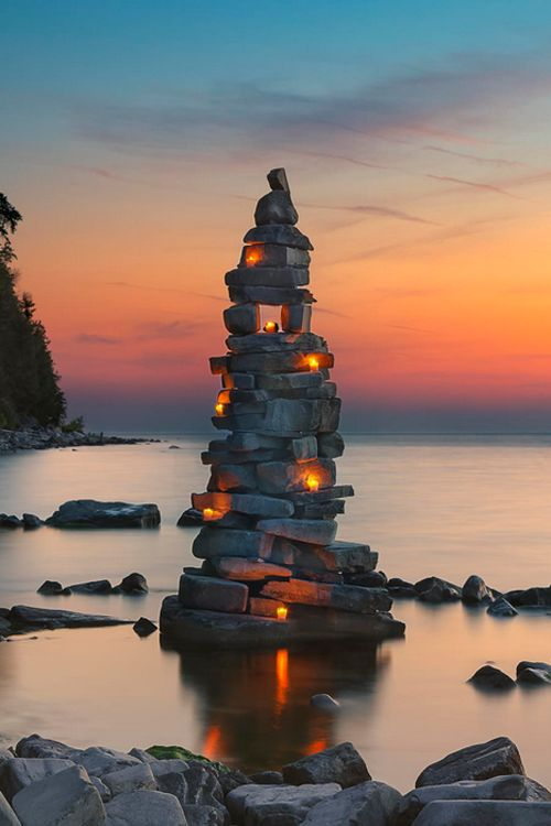 The after glow of the sun over Green Bay accents the glowing candles on stacked stones - Wisconsin, USA (by Dave Biermann)