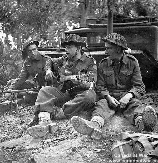 Canadians capture Caen - Pte. W.J. Lutz, Pte. J.D. Hines (with guitar), and Pte. R. Lecoeyer relax beside dugout during break in battle. 10 July 1944, Caen, France.