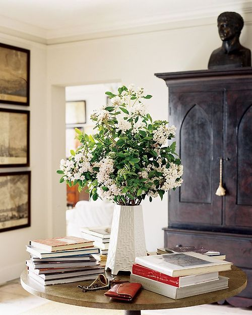 """I'm usually not a fan of stacks of books on a table, but this does look """"put together""""...it may be the beautiful cabinet, with the tassel and the sculpture on top."""