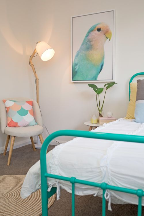 Kids bedroom, aqua metal single bed frame, parrot artwork, round rug, timber floor lamp, white bedding, bright colours
