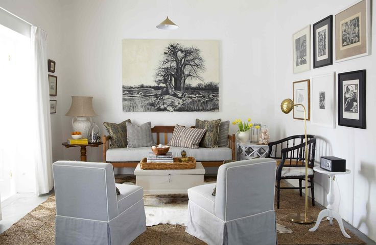 The sitting room with stoep bench and cow skin rug. Charcoal by Kurt Pio. Interiors by Jean-Pierre de la Chaumette.