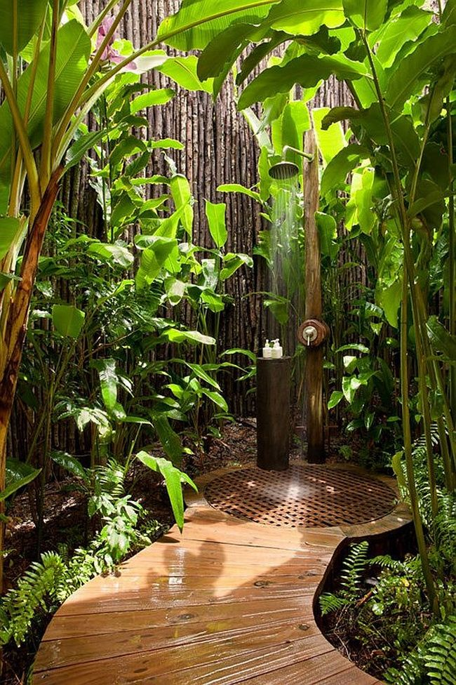 This outdoor waterfall shower makes you feel like you're in the tropics. The curved wooden walkway and all the plants are like paradise. | Tiny Homes