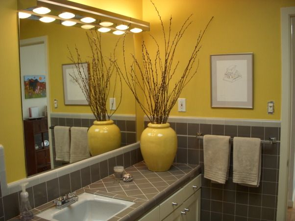 Gray bathroom tiles goes well with the yellow colors on this bathroom.