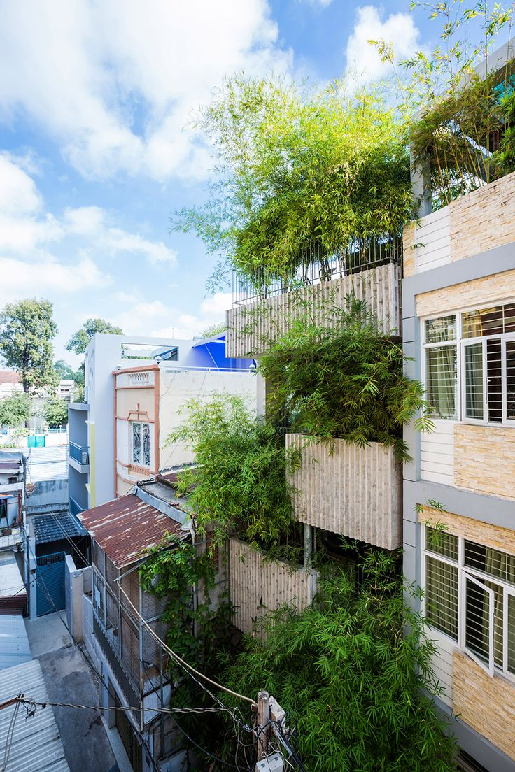 Bamboo plants grow up the front of this slender house in Vietnam's Ho Chi Minh City, which Vo Trong Nghia Architects has covered in huge, grooved concrete planters.