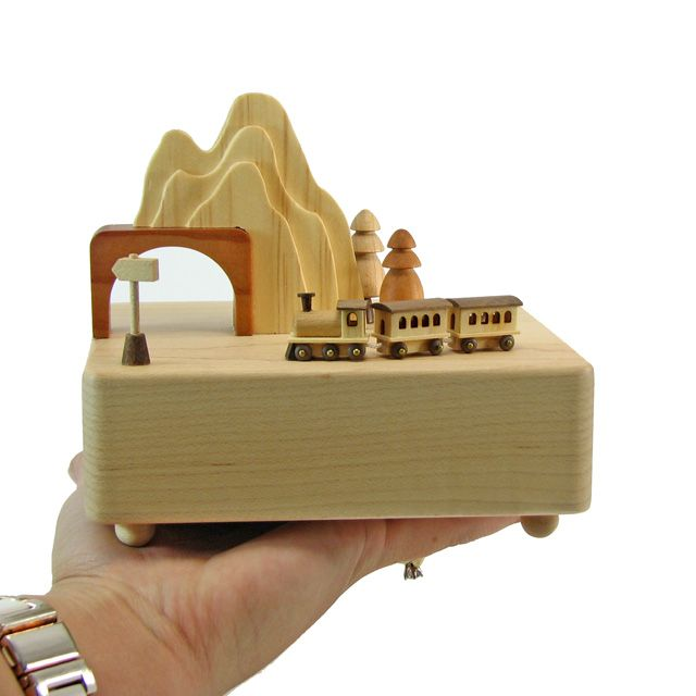 """This unique fine wood crafted music box comes with a miniature train that circles around the music box and through the railroad tunnel according to the rhythm of the music """"I've Been Working on the Ra"""