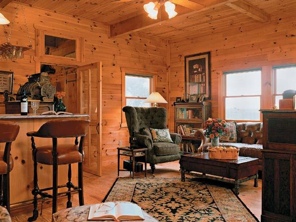 living room with knotty pine walls and overstuffed furniture