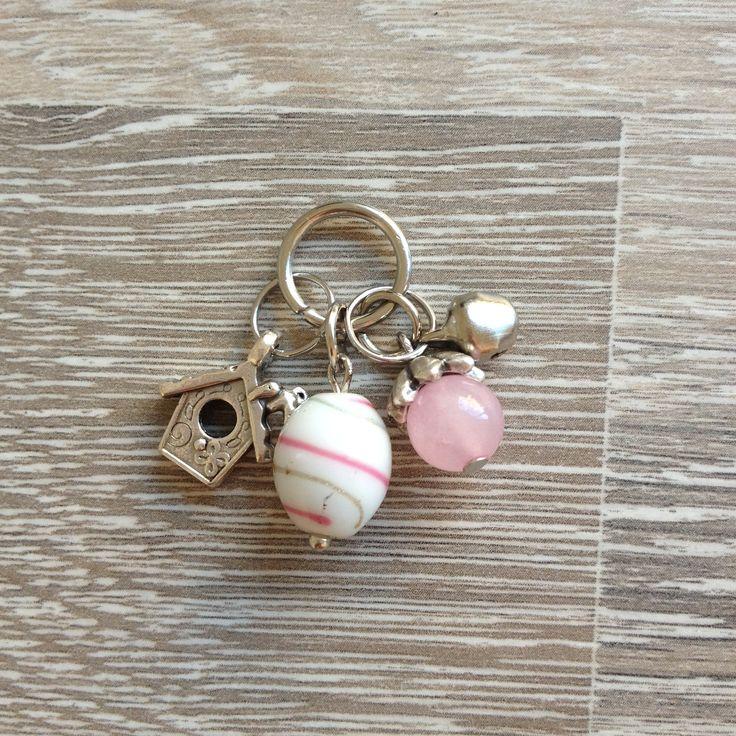 Bedel van metalen belletje, 8mm licht roze opaal met metalen sierkap, witte glaskraal met roze en gouden strepen en een metalen vogelhuisje. Van JuudsBoetiek, €4,00. Te bestellen op www.juudsboetiek.nl.