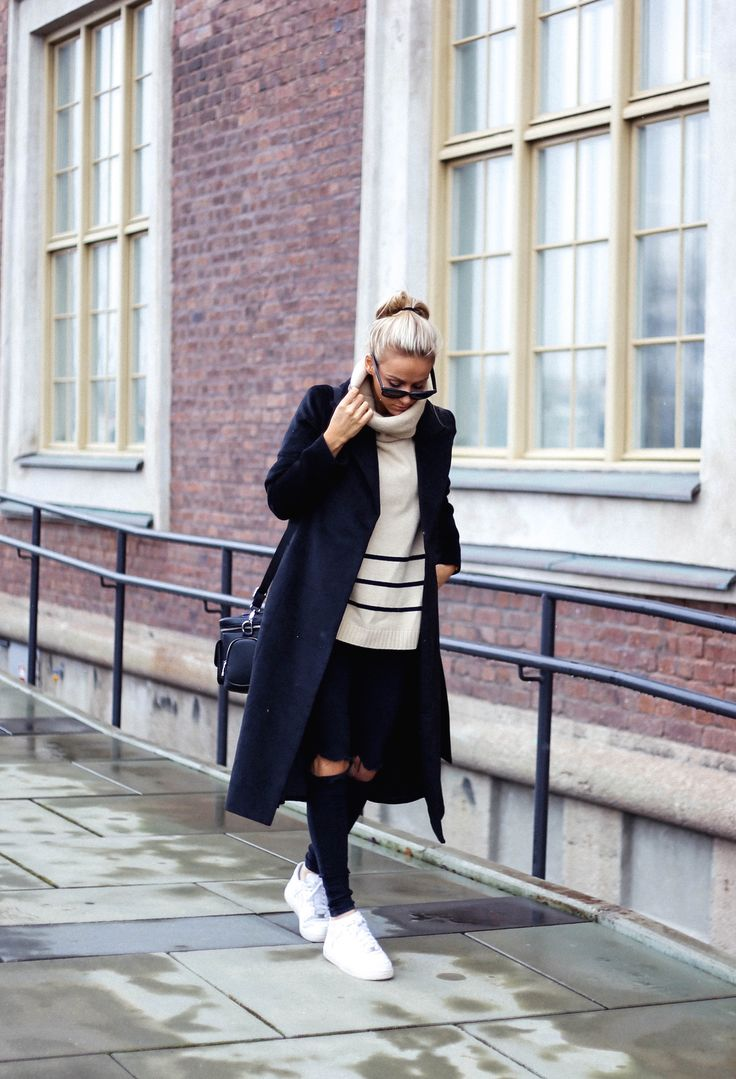 Sendi Skopljak is wearing a black long coat and apricot cape style sweater from from Sheinside, the black ripped jeans are from Dr. Denim and the sneakers are from Nike
