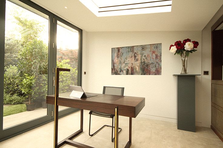 Recessed roller blinds in bifolding doors, skylight and to hide a TV. Contemporary designed office.