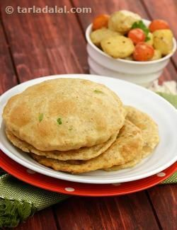 Bhatura are leavened puris usually served with Chole. They are soft and spongy and must be enjoyed while they are hot or else they become chewy. This recipe is a variation of this popular bread that uses a potato filling to add softness to the Bhatura and a blend of other ingredients to flavour them. Moreover the potatoes prevent the Bhatura from turning rubbery and chewy. Another innovation is that they can be cooked lightly on a tava and kept aside. Deep-fry them only when you need to ...