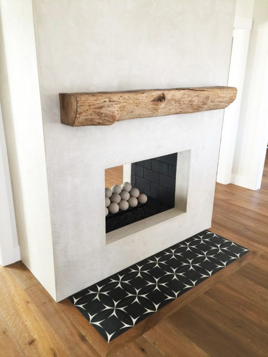 Rustic rough hewn mantel grey stucco fireplace with cement tile hearth.