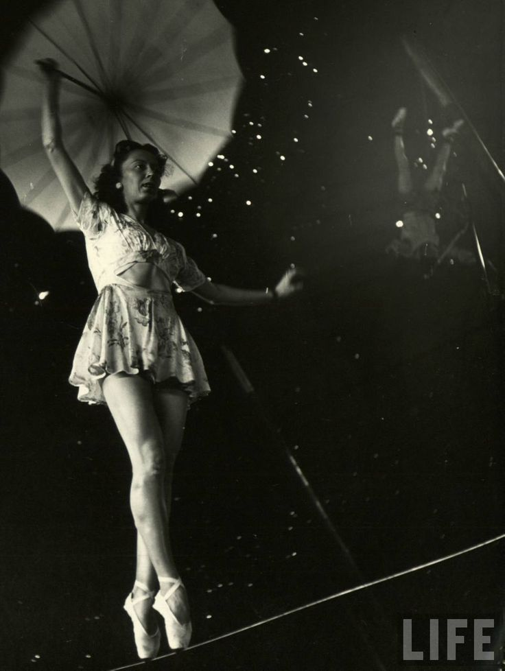 """From a story on the Ringling Bros. Circus in the April 4, 1949, issue of LIFE. The caption for this picture: """"Nothing but circus all day every day is the happy fate of these two performers' tots, who sit around the big tent watching as the pretty Miss Lola practices on a tightwire and an acrobat balances an odd contraption on his feet."""""""
