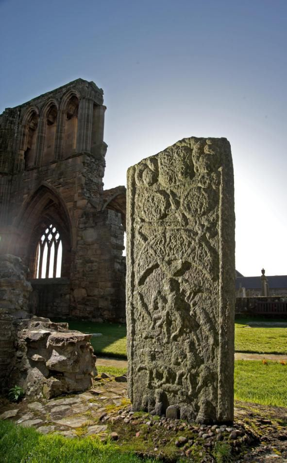 Elgin's Pictish Stone, on the grounds of Elgin Cathedral, Scotland. One side of the stone is overtly Christian, with a carved cross, but the other side is covered with a hunting scene and pagan Pictish symbols including a crescent and z-rod. The stone was found at St Giles parish church in 1823 and moved to the cathedral grounds.
