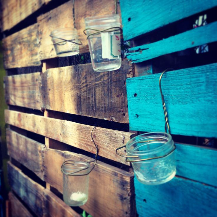 Backyard hanging candle holders made from wire hangers and mason jars.