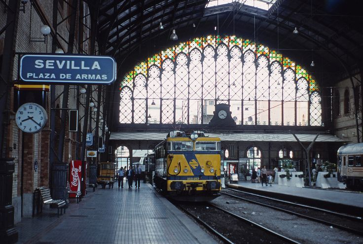 https://flic.kr/p/N9CQyw   Seville P. de Armas   1973-built 269 class Bo-Bo, no. 253, is seen under the incredible roof of the now closed Plaza de Armas station in Seville.  This station closed in the 1990s, or thereabouts, but the magnificent building was retained and is now some sort of posh shopping mall.  June 1990  Honeywell-Pentax H3v/ 55mm f1.8 Super Takumar lens Kodachrome 64