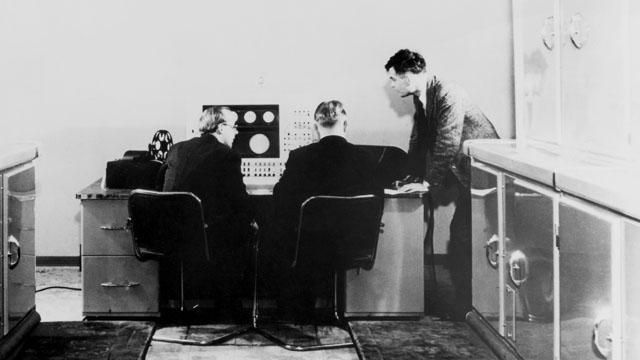 Alan Turing with two colleagues and a Ferranti computer in January 1951. Turing had previously been involved with the construction of both the Colossus at Bletchley Park, and later the Automatic Computing Engine