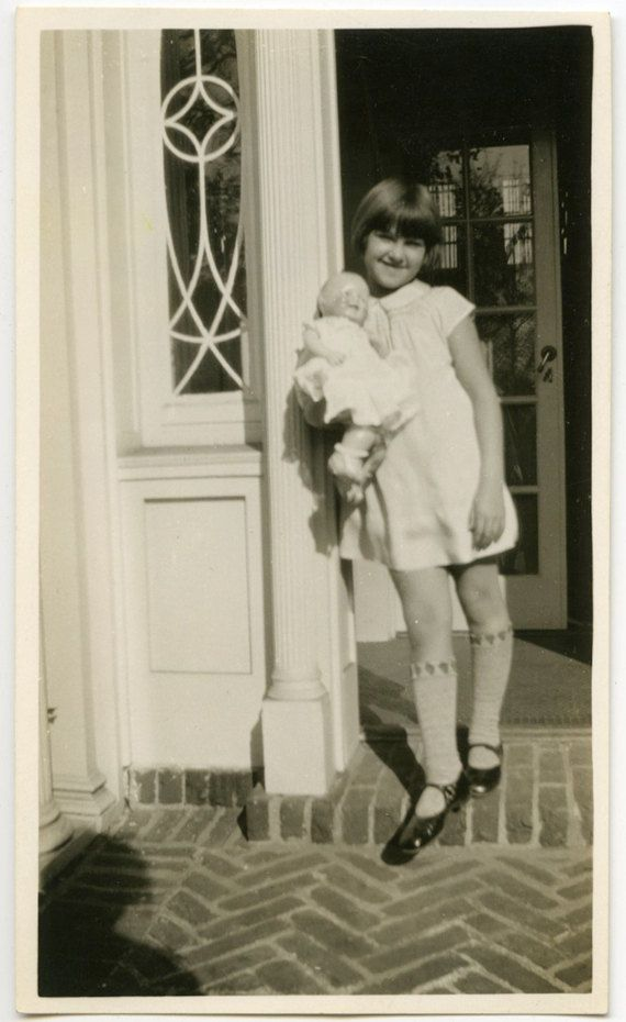 Girl posing holding her baby doll -- (this was labeled as being from the 1920's by another Pinner, but judging from the girl's very short dress, I think it more likely from a later period, perhaps around the 1960's)