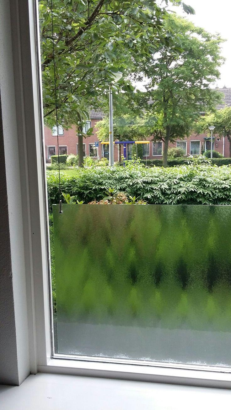Glasplaat voor het raam. Deze hangt aan twee stalen kabeltjes. Om inkijk te voorkomen.