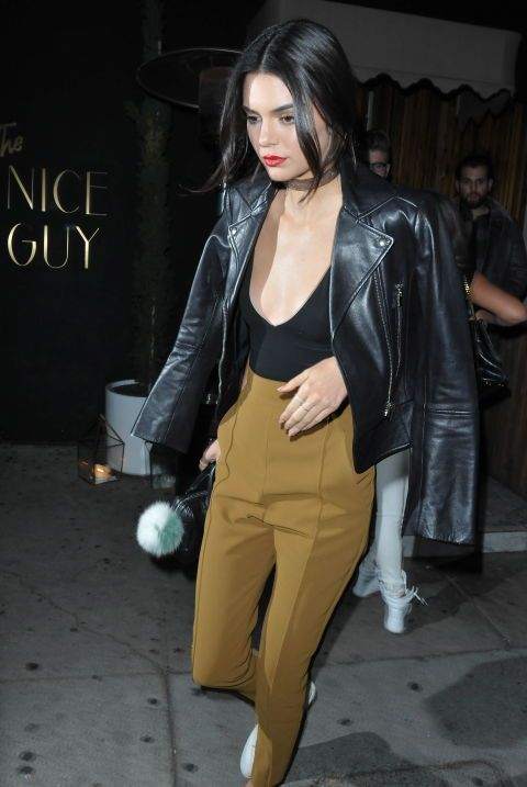 Jenner's choker and red lip combo is enough to amplify any outfit, but she kept the chic coming in a leather jacket worn on the shoulders, plunging black tank top, high-waisted khaki-hued-trousers, and white trainers.