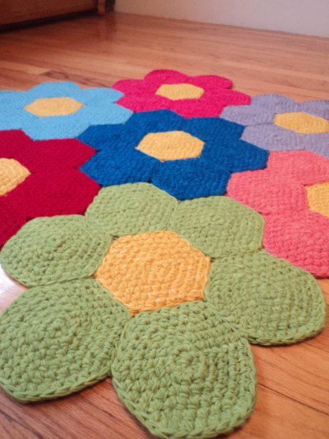 This Flower rug was made with a lot of care and love! I personally dyed the wool to make this rug then crocheted and sewed it together. It is such a fun and colorful rug, to brighten up a bedroom or play room.  Measurements: 3 feet wide (three flowers across)  Colors: Lime green, peach, pink, red, lavender purple, baby blue and med blue  Made with 100% wool.    Made in a smoke free, pet friendly home.  Shipping cost is for Priority mail. The rug is rather heavy and this would be the cheapest…