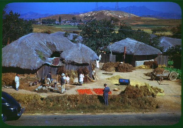 Korean farm village - a thatched house near and a cluster of other houses far by a hill. Undated. Nam Young Chung Collection. Ctr for Korean Studies Digital Archive, Manoa, Hawaii.