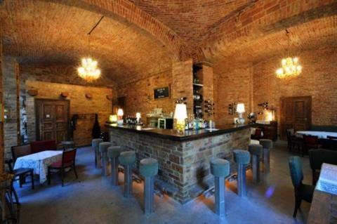 Color photo of empty bar. Brick walls, stools