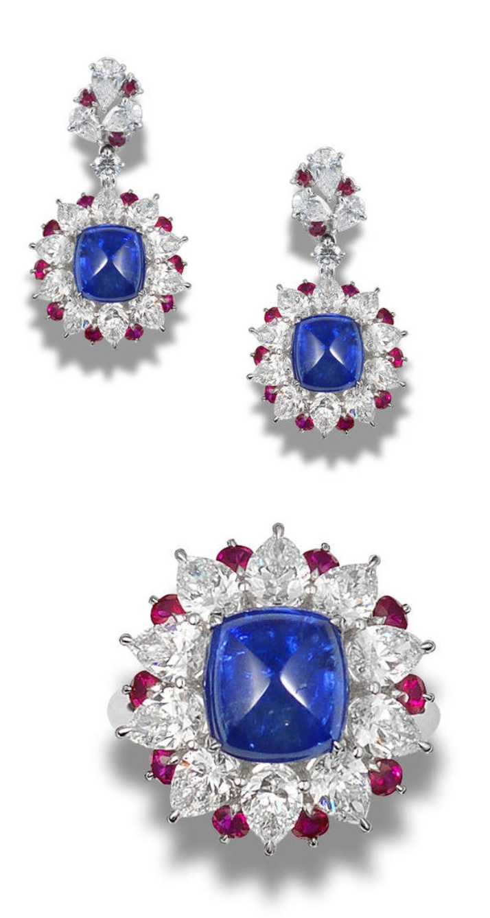 diamond and ruby ring and earring suite The ring set with a sugarloaf sapphire weighing approximately 6.28 carats, within a pear-shaped diamond surround, accented with circular-cut rubies, to a reverse set with brilliant-cut diamonds, accompanied by a pair of matching earrings, mounted in platinum