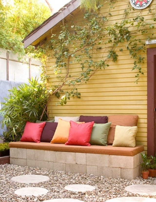 Great idea. Cinderblocks stacked up against a wall with a cushion on top. Easy!
