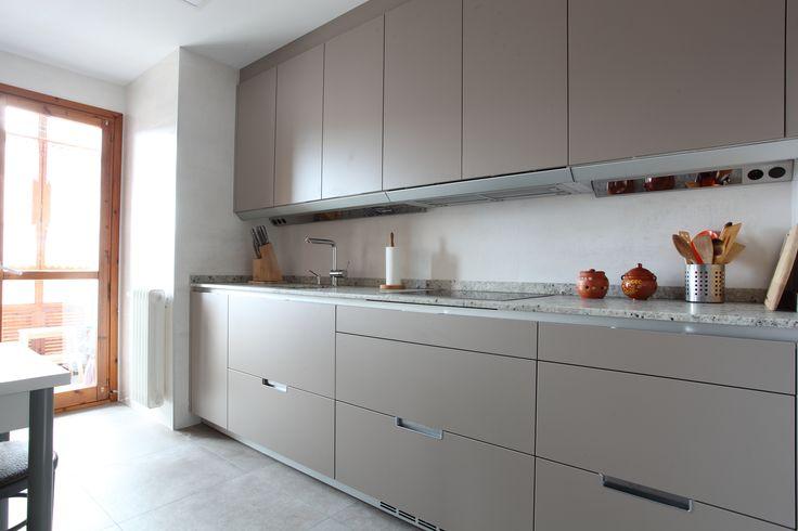 Cocina SANTOS Modelo MINOS-E en color Gris ARENA, cierre a techo, integracion de electrodomesticos, perfil de iluminacion y encimera Granito Warwick Saten. Proyecto by FOCARIS