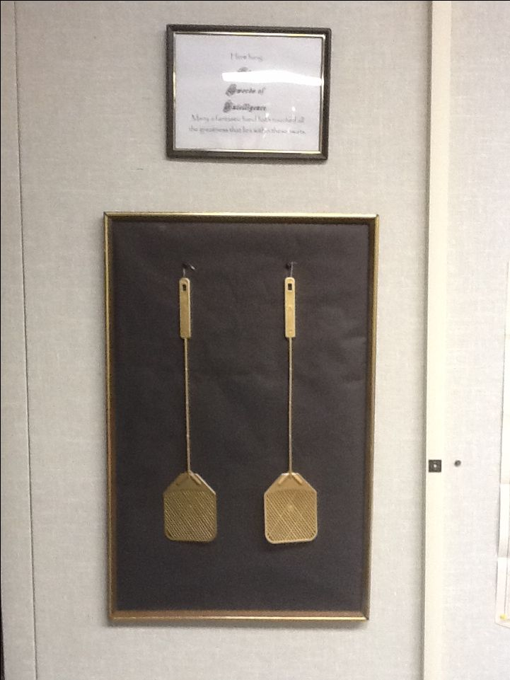 "My High School classroom decor - these are the ""Swords of Intelligence"" we use for quick team quizzes - the sign reads ""Here hang the Swords of Intelligence - Many a fantastic hand hath touched all the greatness that lays within these swats."" if I remember correctly. I just had it written up there and a student made me the print out :-) more official, I guess. Yes, I spray painted them gold. Nerd."