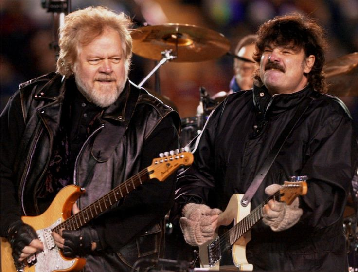 Randy Bachman, left, and Burton Cummings of The Guess Who reunite during the halftime show at the 88th Grey Cup game in Calgary, on Nov. 26, 2000 | Aaron Harris / THE CANADIAN PRESS file photo