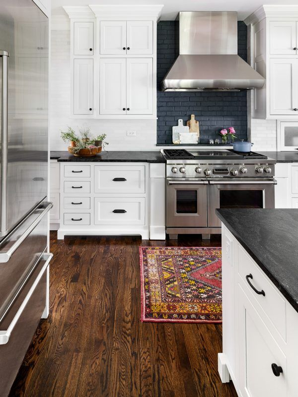 White Kitchen Cabinets Dark Wood Floors Vintage Rug Black Marble Countertops Stainless Stee Interior Design Kitchen Kitchen Design Styles Kitchen Style