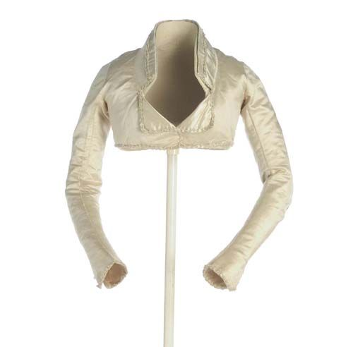 "[via google translate] ca. 1795-1815 Spencer silk satin ivory. Below the chest, neck placket and flap in the front. The sleeve, long and narrow, shaped at the elbow. Is decorated with bodkins of chenille, and back, at the start of the skirt, topped with pompom tassels This garment short call Spain doublet was also known by the international voice ""spencer"". As a jacket, appearing around 1795 as a pledge over the ""white shirt"". Museo del Traje."
