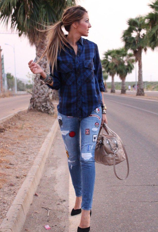 Camisa azul a cuadros, jeans azules con rotos y parches.